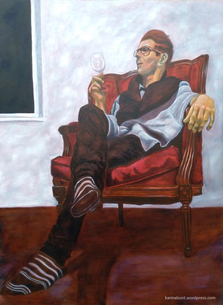 Junger Mann im Lehnsessel sitzend, ein leeres Weinglas in der Hand