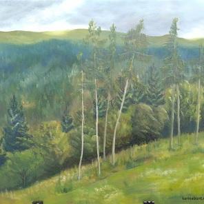 Berge mit Wald und einzelnen Bäumen im Vordergrund